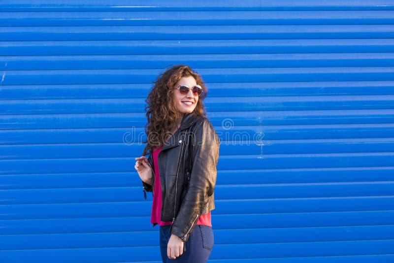 Utomhus stående av en härlig ung kvinna med moderna sunglas royaltyfri foto