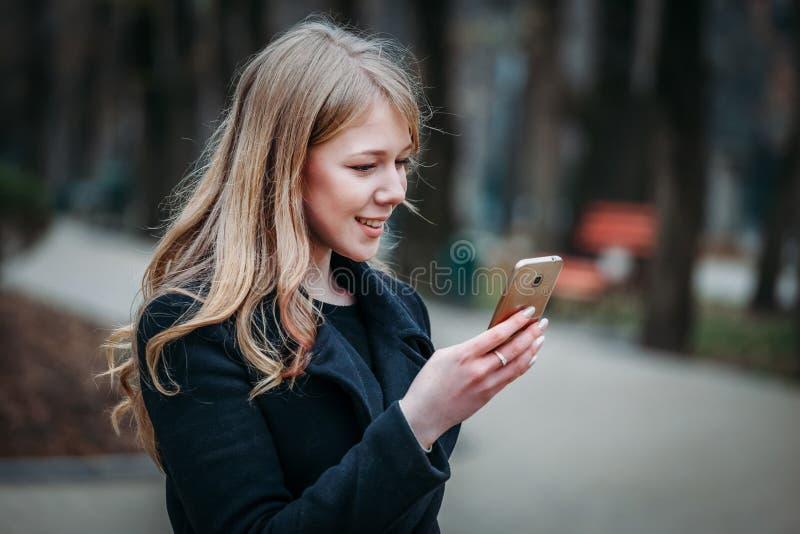 Utomhus- stående av en långhårig kvinna för romantisk nätt elegant affär som tycker om en promenad till och med staden med en tel arkivbild