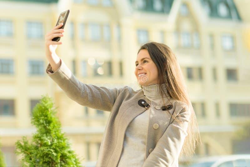 Utomhus- stående av en le lycklig ung kvinna med smartphonen, stadsgatabakgrund, solig dag för höst Flickan gör selfiefotoet royaltyfri fotografi