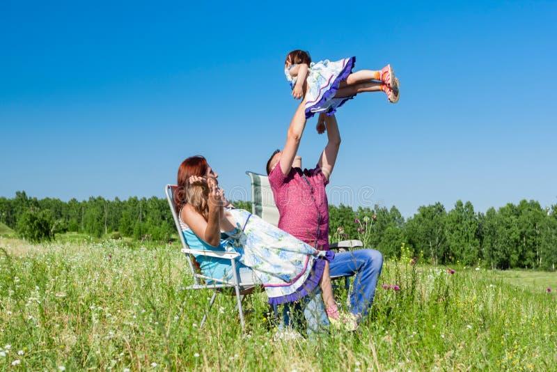 Utomhus- stående av en lycklig familj fadern valde upp barnet i henne armar royaltyfria bilder