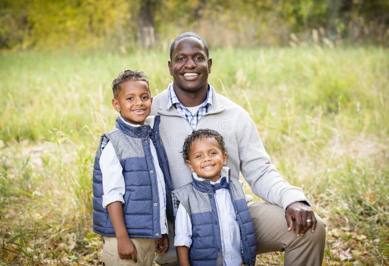 Utomhus- stående av en Racially olik fader med hans två söner royaltyfria bilder