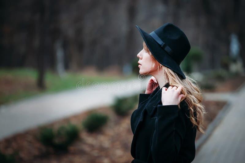 Utomhus- stående av en romantisk nätt elegant affär av en långhårig kvinna som tycker om en promenad till och med staden Foto av  royaltyfri foto