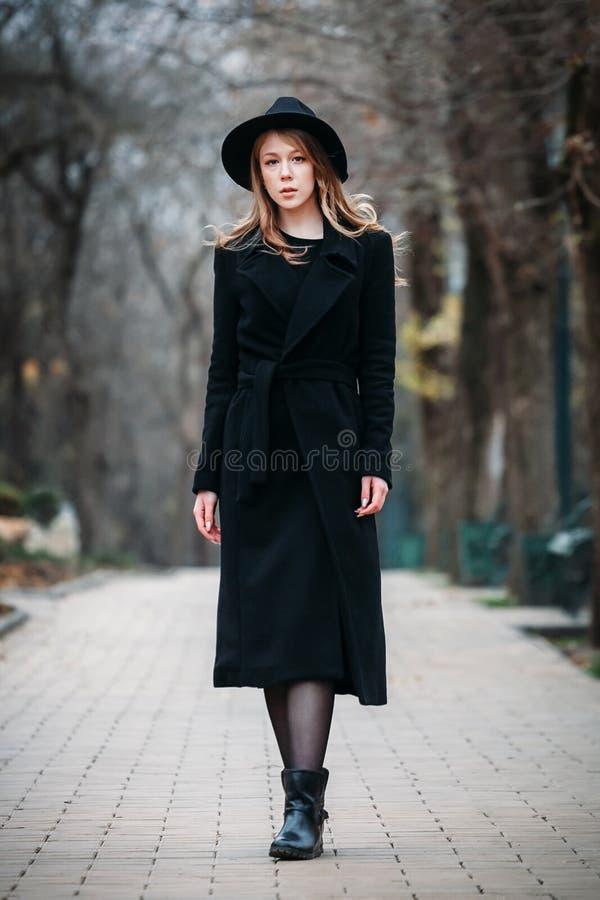 Utomhus- stående av en romantisk nätt elegant affär av en långhårig kvinna som tycker om en promenad till och med staden arkivbild