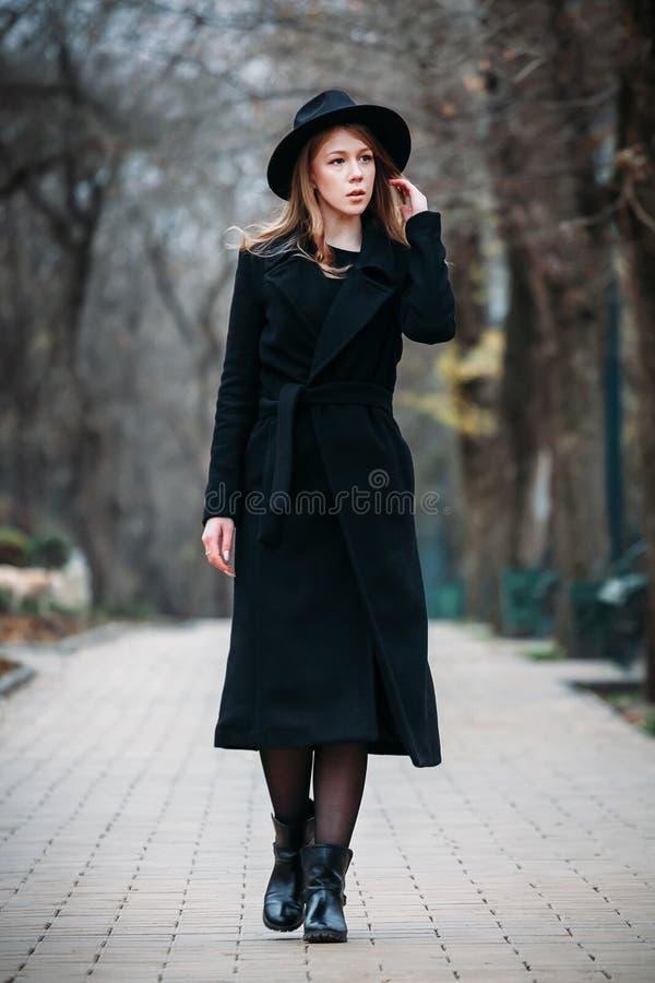 Utomhus- stående av en romantisk nätt elegant affär av en långhårig kvinna som tycker om en promenad till och med staden royaltyfria bilder