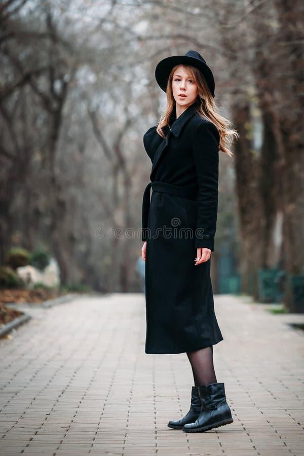 Utomhus- stående av en romantisk nätt elegant affär av en långhårig kvinna som tycker om en promenad till och med staden royaltyfri bild