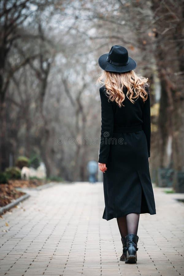 Utomhus- stående av en romantisk nätt elegant affär av en långhårig kvinna som tycker om en promenad till och med staden arkivbilder