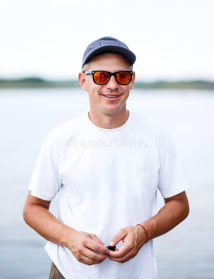 Utomhus- stående av en stilig ung man i jeans och den vita t-skjortan fotografering för bildbyråer