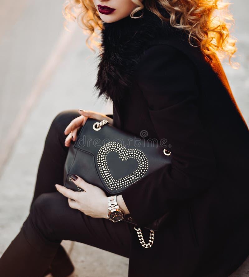 Utomhus- stående av en ung härlig trendig dam som går på gatan Modell som bär stilfull kläder Kvinnligt dana royaltyfri fotografi