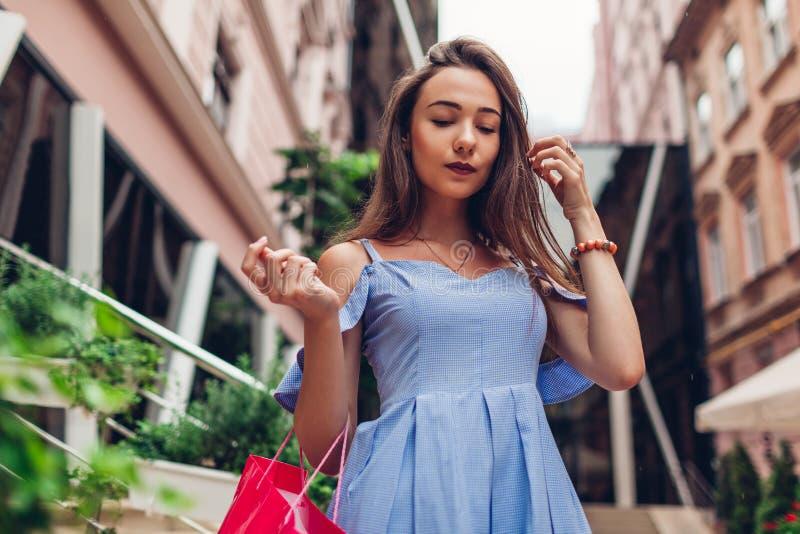Utomhus- stående av en ung härlig trendig kvinna som går med shoppingpåsen på stadsgatan vid köpcentret royaltyfri foto