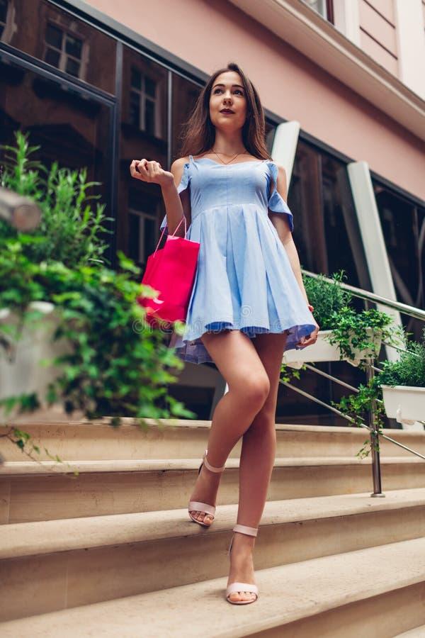 Utomhus- stående av en ung härlig trendig kvinna som går med shoppingpåsen på stadsgatan vid köpcentret arkivfoto