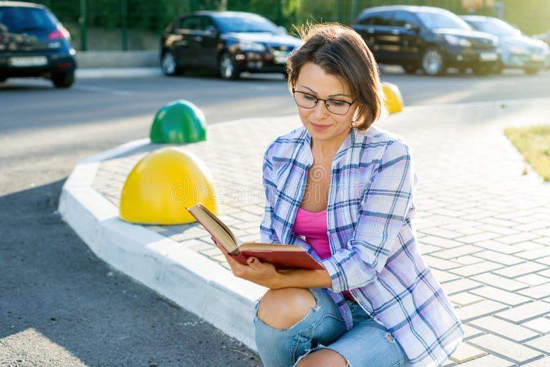 Utomhus- stående av en vuxen härlig kvinna som läser en bokwhil royaltyfria foton