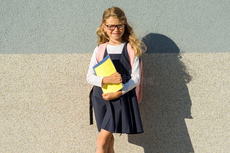 Utomhus- stående av flickagrundskolaeleven, bärande exponeringsglas, med ryggsäcken, böcker och anteckningsböcker, grå vägg för b royaltyfri bild