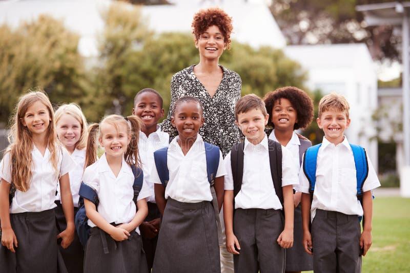 Utomhus- stående av grundskolaelever med läraren Wearing Uniform Standing på spelplan fotografering för bildbyråer