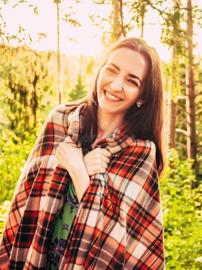 Utomhus stående av härliga le den bakbelysta brunettflickan Härlig caucasian brunettflicka som slås in i ett rutigt royaltyfri foto