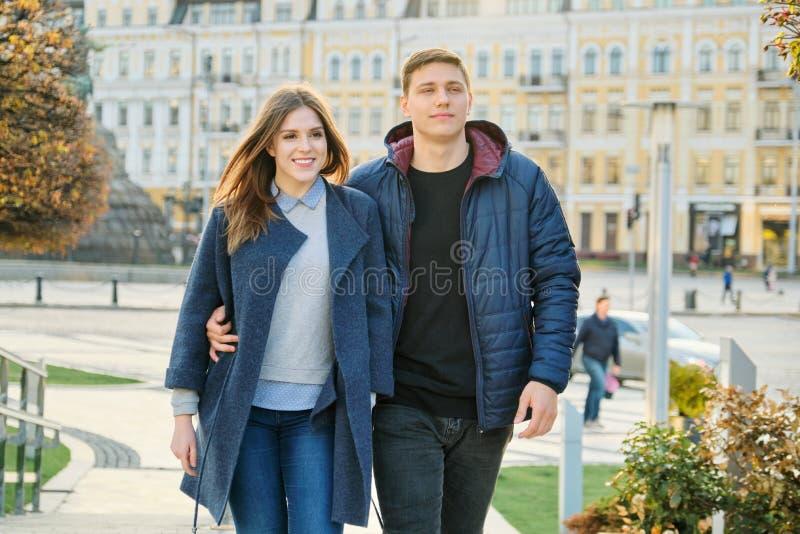Utomhus- stående av lyckliga omfamna par, den stiliga mannen och kvinnan som går, bakgrundsaftonstad royaltyfria bilder
