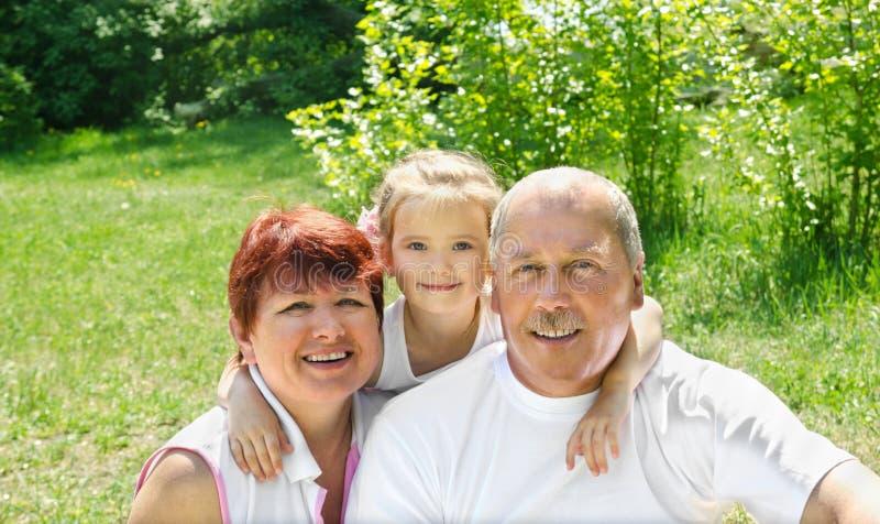 Utomhus stående av morföräldrar med sondottern arkivbilder