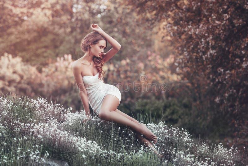 Utomhus- stående av sammanträde för ung kvinna på fältet royaltyfria foton