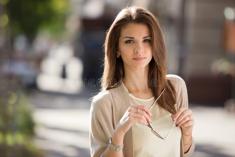 Utomhus- stående av skönhetkvinnan med perfekt leendeanseende på gatan royaltyfri bild