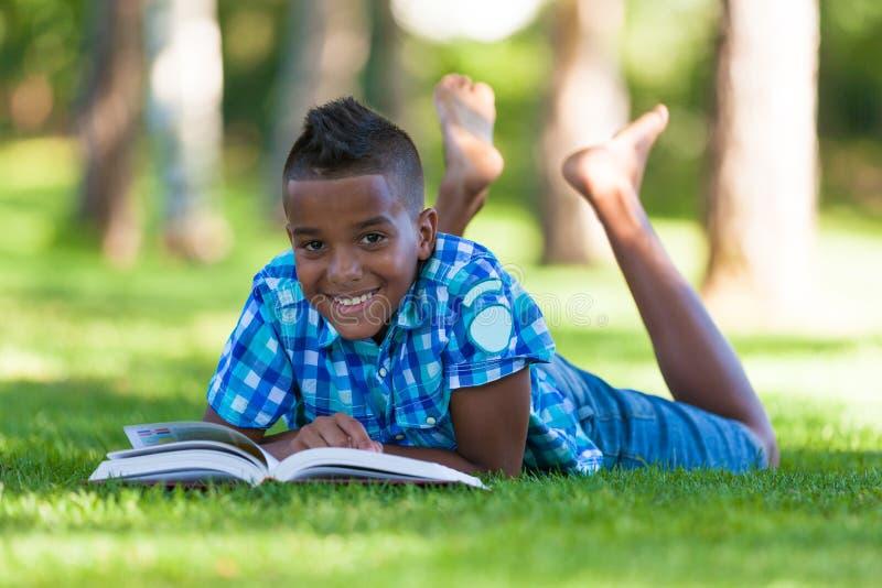 Utomhus- stående av studentsvartpojken som läser en bok royaltyfri foto