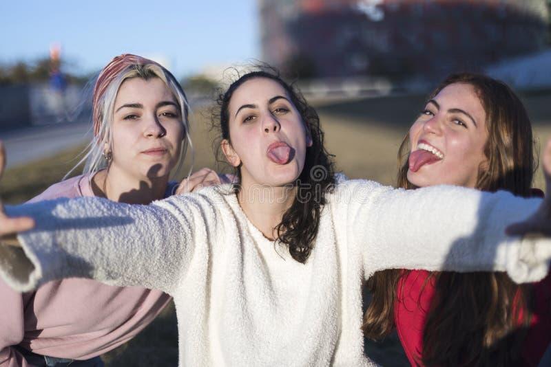 Utomhus- stående av tre roliga flickor för vänner som tar foto med en smartphone på den ljusa solnedgången royaltyfri fotografi