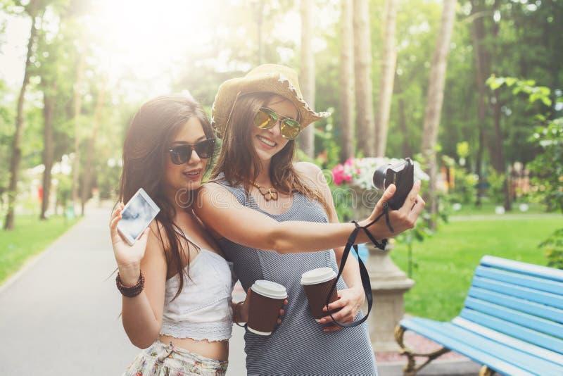 Utomhus- stående av tre vänner som tar foto med en smartphone arkivbilder
