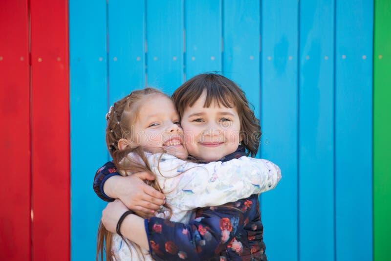 Utomhus- stående av två omfamna gulliga små flickor royaltyfria foton