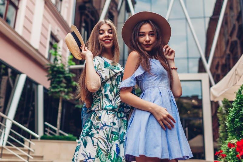 Utomhus- stående av två unga härliga kvinnor Flickor som bär stilfull kläder och tillbehör i stad Bästa vän royaltyfri foto