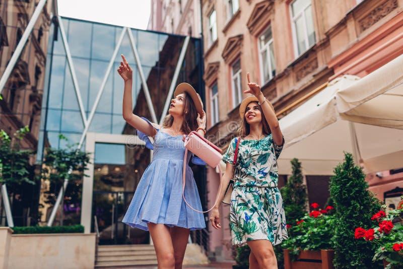 Utomhus- stående av två unga härliga kvinnor som går på stadsgatan Bästa vän som hänger och att ha gyckel royaltyfri foto