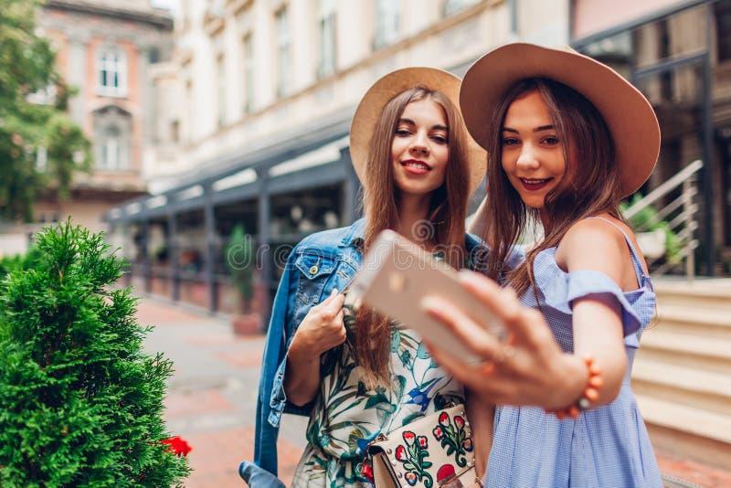 Utomhus- stående av två unga härliga kvinnor som tar selfie genom att använda telefonen Flickor som har gyckel i stad Bästa vän royaltyfria foton
