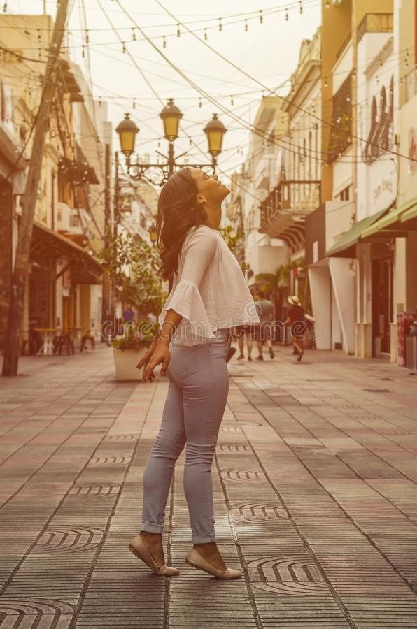 Utomhus- stående av unga härliga gammalt posera för flicka 9 till 25 år i gata bärande vit blus och åtsittande jeans arkivfoto