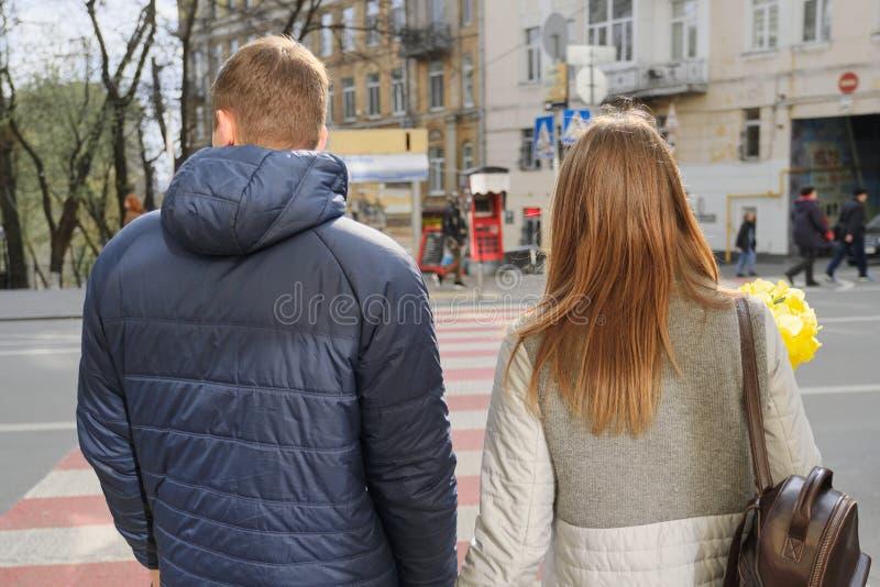 Utomhus- stående av unga par som går på stadsgatan, lycklig ung man och kvinna på zebramarkeringen, tillbaka sikt, stads- bakgrun arkivbild
