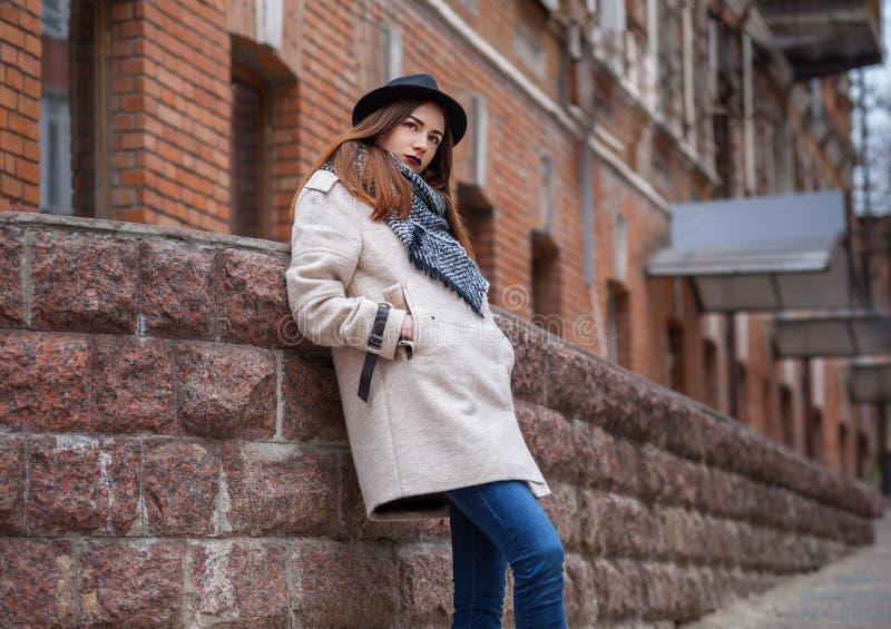 Utomhus- stående för mode av den sexiga romantiska damen för glamour som bär det tillfälliga laget, svart hatt Kall vårhöstsäsong royaltyfria foton
