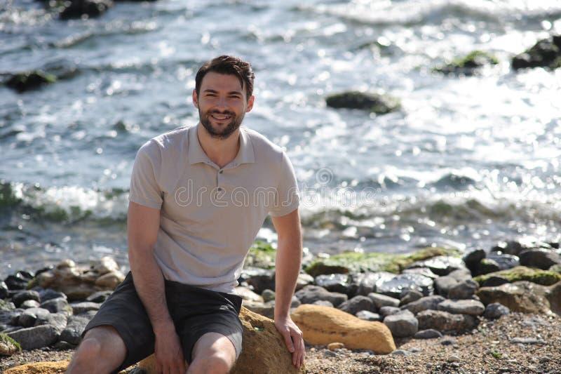Utomhus- stående för ung stilfull man, vit poloskjorta som sitter på en sten royaltyfri fotografi