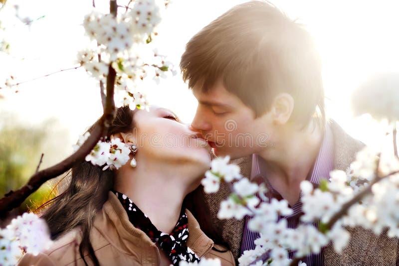 Utomhus- stående för vår av ungt kyssa för par royaltyfri fotografi
