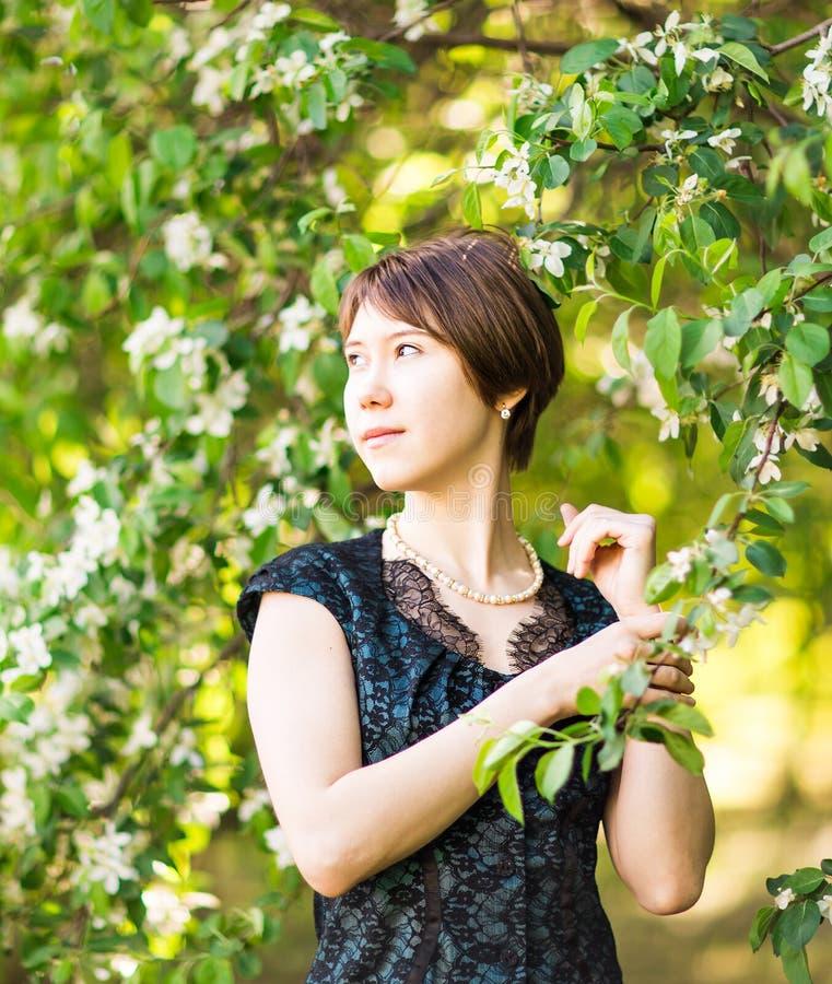 Utomhus- stående för vårflicka i blommande träd Romantisk kvinna för skönhet i blommor sinnlig lady härlig kvinna arkivfoto