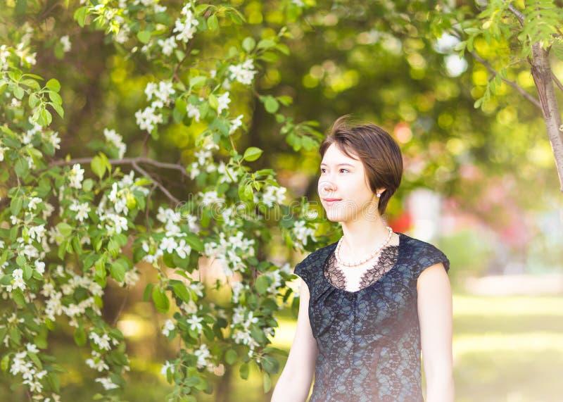 Utomhus- stående för vårflicka i blommande träd Romantisk kvinna för skönhet i blommor sinnlig lady härlig kvinna royaltyfria foton
