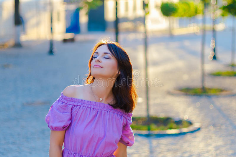 utomhus- stående Ung härlig kvinna som är borttappad i tanke, medan besöka centret på en solig dag, i en purpurfärgad klänning me royaltyfria foton