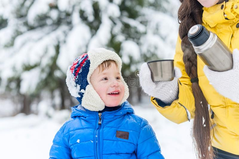 Utomhus- ståendemoder och lycklig son som dricker te från ett thermo arkivbilder