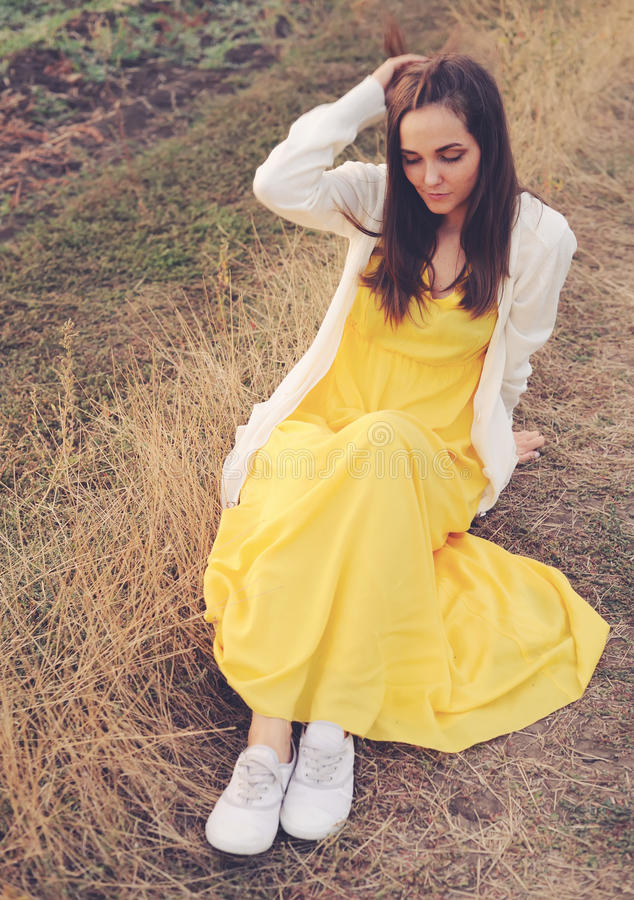 Utomhus- ståendesammanträde för ung kvinna på ett deadwoodfält arkivfoto