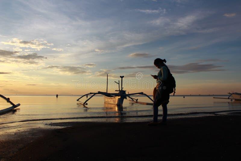 utomhus- ståendesolnedgångkvinna royaltyfria foton