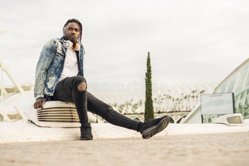 Utomhus- st?ende av en stilig och attraktiv ung afrikansk man med musikh?rlurar p? gatan arkivfoton