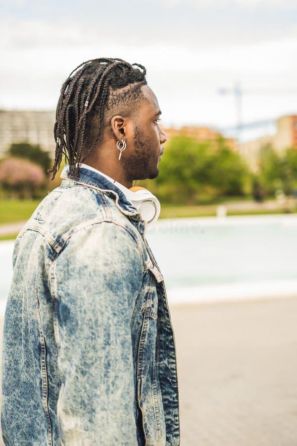 Utomhus- st?ende av en stilig och attraktiv ung afrikansk man med musikh?rlurar p? gatan royaltyfri foto