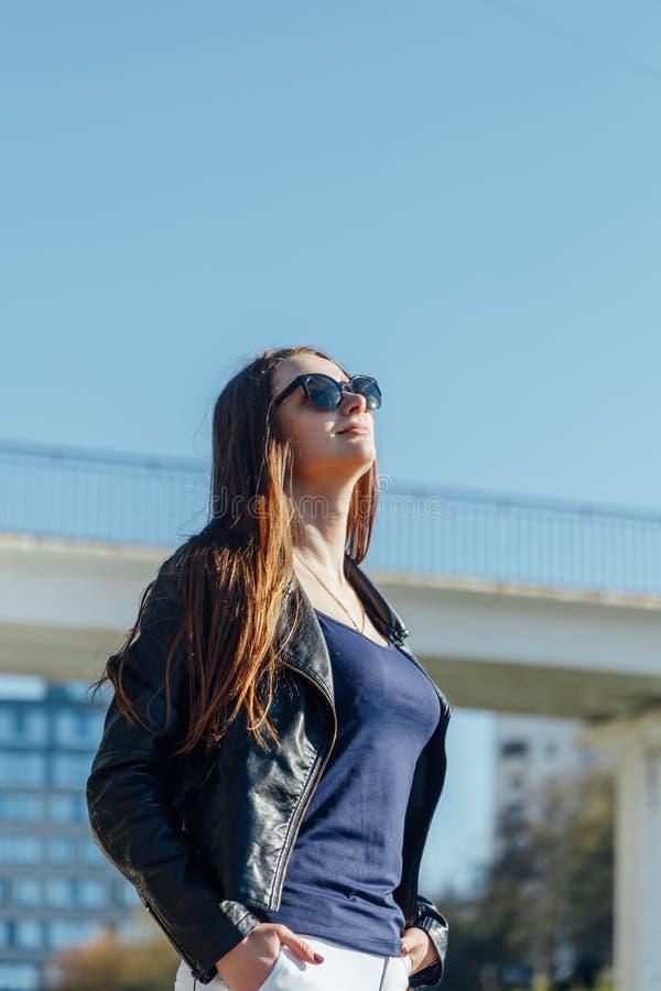 Utomhus- st?ende av en ung h?rlig s?ker kvinna som poserar p? gatan arkivfoto