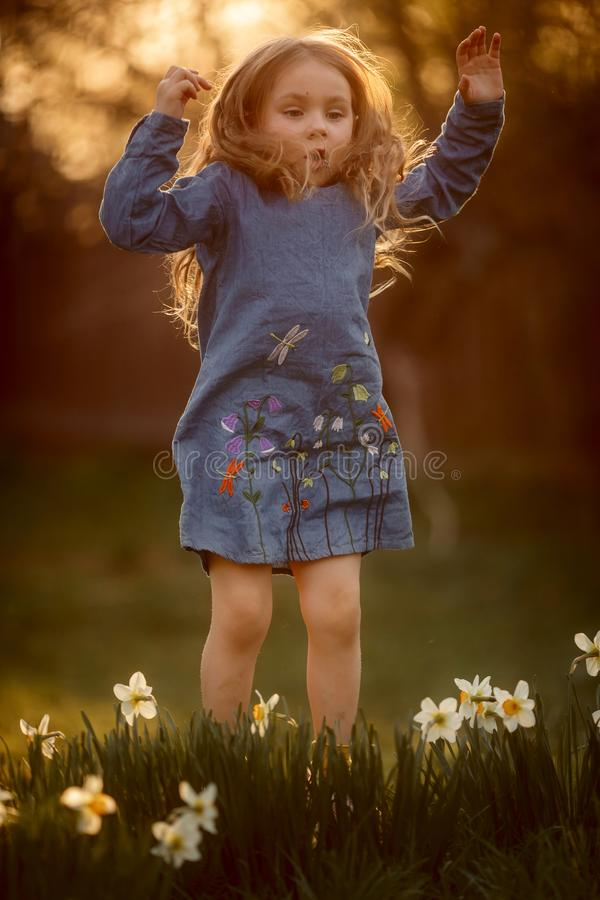 Utomhus- st?ende f?r liten flicka n?ra pingstliljablommor p? solnedg?ngen arkivbild