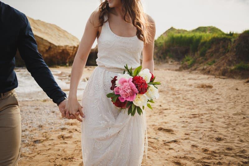 Utomhus- strandbröllopceremoni nära havet, slut upp av händer av stilfulla par med bröllopbuketten, brud är royaltyfria bilder