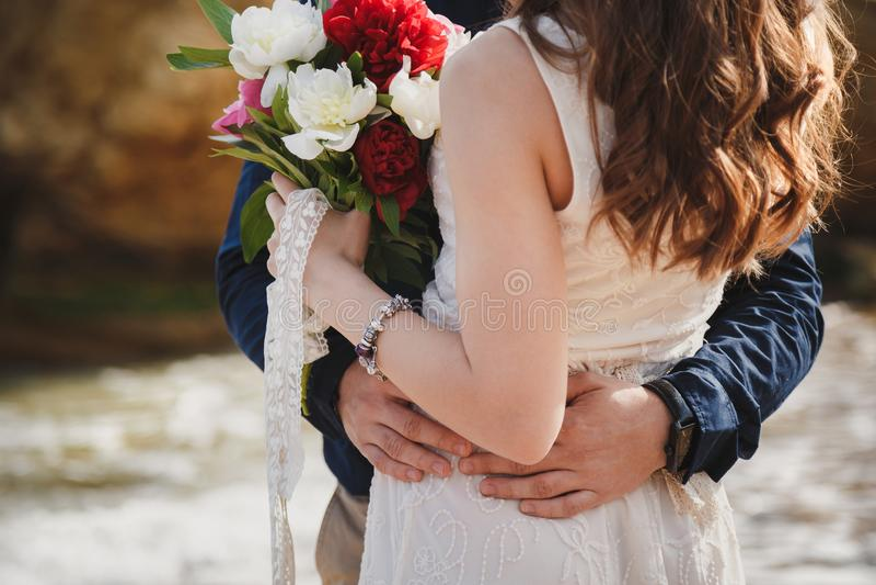 Utomhus- strandbröllopceremoni nära havet, slut upp av omfamningen av stilfulla par med bröllopbuketten, man kramar bruden arkivbild