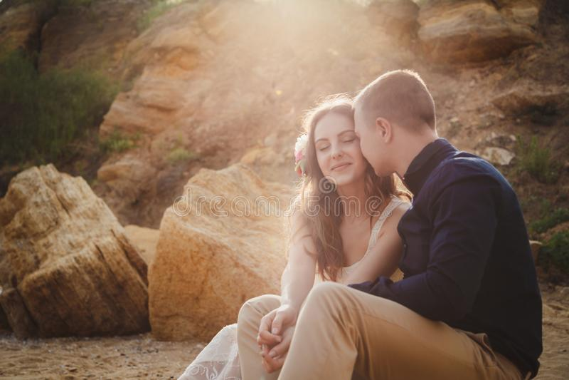 Utomhus- strandbröllopceremoni, slut upp av stilfulla lyckliga romantiska par som sitter tillsammans i solljus royaltyfri foto