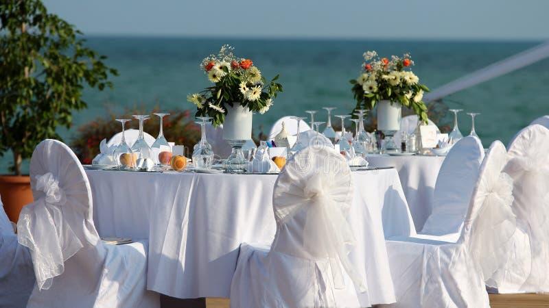 Utomhus- tabellinställning på bröllopmottagandet vid havet arkivbilder