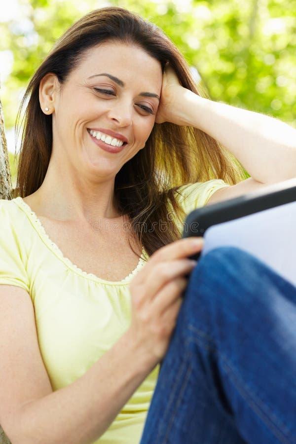utomhus tablet genom att använda kvinnan royaltyfria bilder
