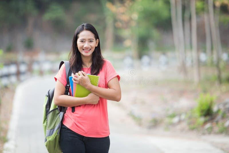 Utomhus- ung asiatisk student och att posera cutely till kameran royaltyfri fotografi